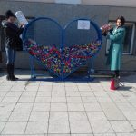г-жа Коцева и г-жа Даковска, помагат за изсипването на капачките в голямото сърце